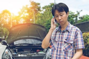 Mann, der um Hilfe mit einem aufgegliederten Auto anruft