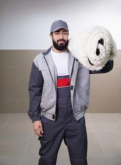 Mann, der uniform steht, die mit einer teppichrolle auf seiner schulter steht