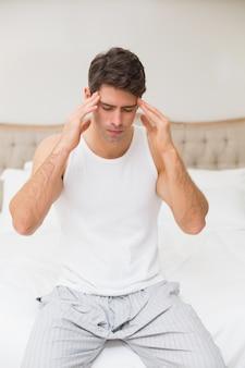 Mann, der unter kopfschmerzen im bett leidet