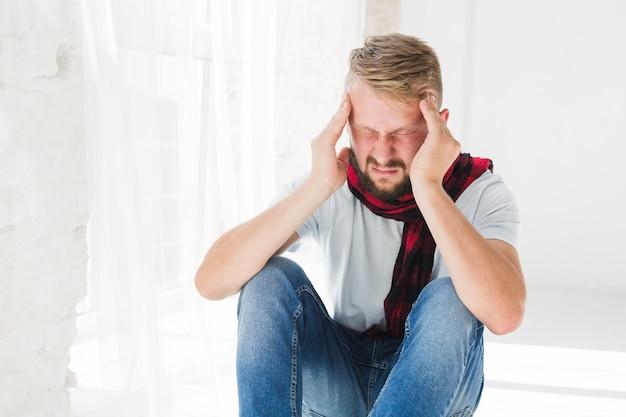 Mann, der unter kopfschmerzen leidet
