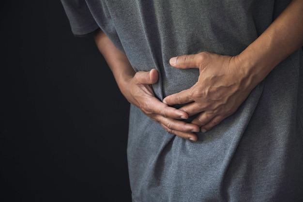 Mann, der unter magenschmerzenschmerzen, magenschmerzen von mann und gesundem konzept leidet.