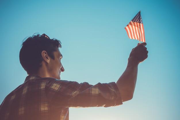 Mann, der usa-flagge hält. unabhängigkeitstag von amerika feiern