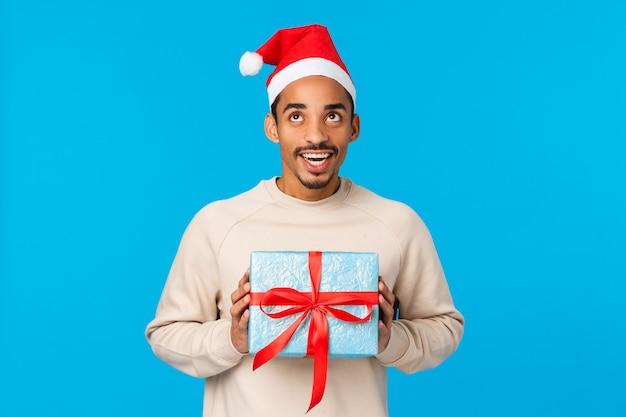 Mann, der verpacktes geschenk schüttelt, wundert sich, was drin ist, erraten. fröhlicher und optimistisch lächelnder afroamerikaner