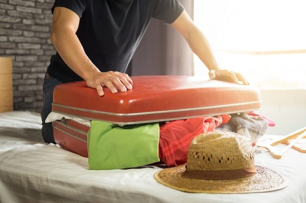 Mann, der versucht, alle kleidung zum verpacken seines roten koffers zu passen