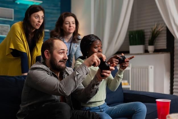 Mann, der versucht, multiethnische freunde bei online-spielen zu schlagen, während er gesellig ist. gemischte rassengruppe von menschen, die spät in der nacht im wohnzimmer zusammen spaß haben.
