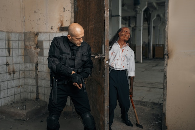 Mann, der versucht, zombie, albtraum in verlassener fabrik zu töten. horror in der stadt, gruselige krabbeltiere, weltuntergangsapokalypse, blutiges böses monster