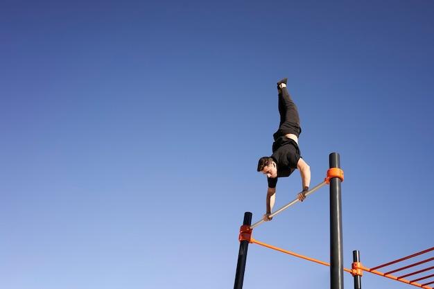 Mann, der vertikalen handstand auf stange tut. bewegung im freien. konzept von gesundem leben, sport, training, krafttraining.