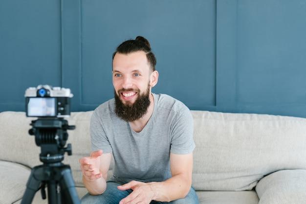 Mann, der video von sich selbst mit kamera auf stativ schießt. lächelnder bärtiger hipster-typ, der mit abonnenten kommuniziert.