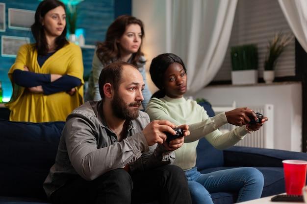Mann, der videospiele mit multiethnischen freunden mit drahtlosem controller spielt. gemischte rassengruppe von menschen, die spät in der nacht im wohnzimmer zusammen spaß haben.