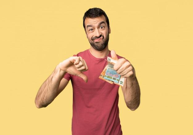 Mann, der viel geld macht gut-schlechtes zeichen nimmt. unentschieden zwischen ja oder nicht auf gelbem hintergrund