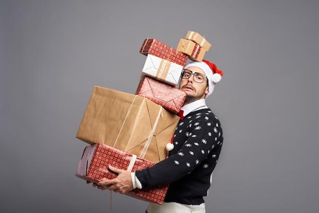 Mann, der viele weihnachtsgeschenke trägt