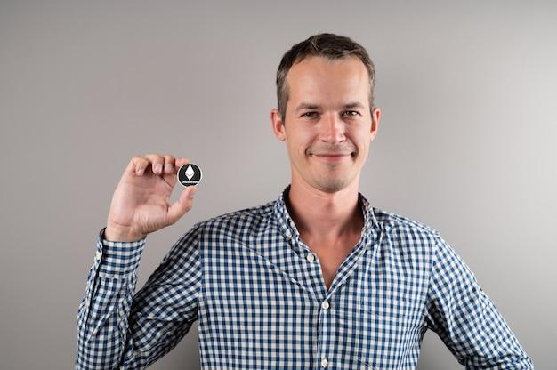 Mann, der virtuelle währung-ethereum-münze hält und lächelt. kryptowährungskonzept.