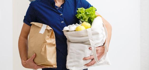 Mann, der volle tüte mit verschiedenen gesunden lebensmitteln auf einem holztisch in der heimischen küche hält, nahaufnahme