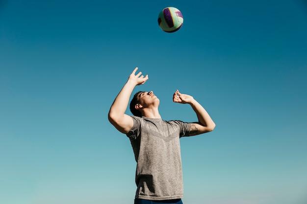Mann, der volleyball am strand spielt