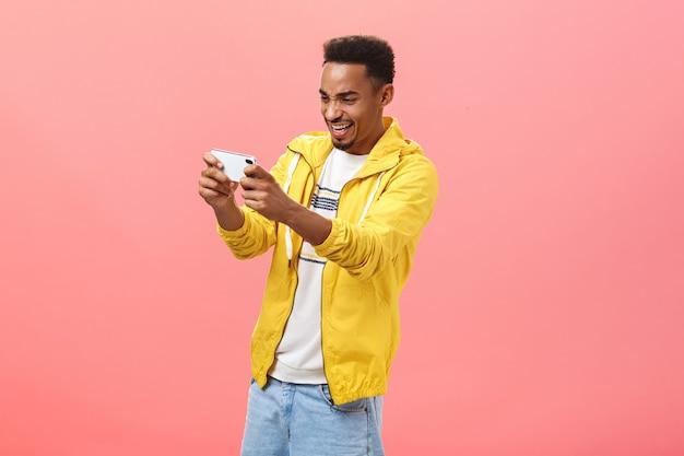 Mann, der von einem coolen smartphone-spiel mitgerissen wird, das ein handy hält, wobei beide hände auf den gerätebildschirm zeigen und auf das gerät starren, mit intensivem erstauntem ausdruck, der auf rosafarbenem hintergrund posiert