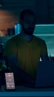 Mann, der von einem intelligenten haus mit einem automatisierten beleuchtungssystem arbeitet