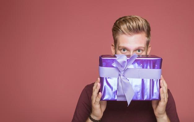 Mann, der von eingewickelter geschenkbox mit dekorativem bogen späht