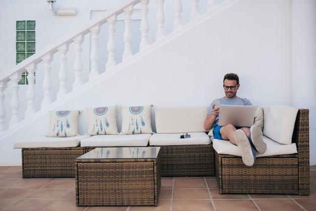 Mann, der von zu hause auf dem hof an seinem computer arbeitet