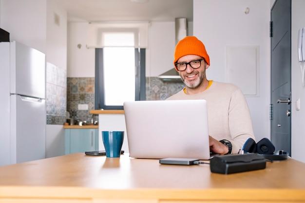 Mann, der von zu hause auf einem laptop arbeitet, der an einem schreibtisch sitzt, der das internet surft