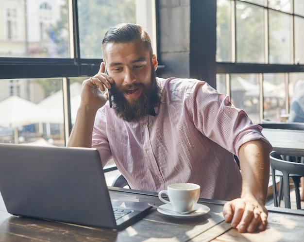 Mann, der vor dem computer sitzt und auf einem mobiltelefon spricht