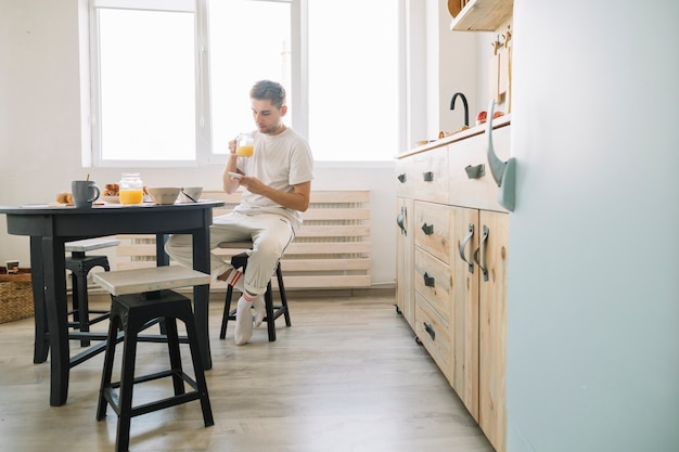 Mann, der vor dem esstisch isst saft unter verwendung des handys sitzt