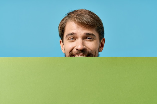 Mann, der vor ihm und grünes banner beschnittenes ansichtsmarketing isolierte form hält