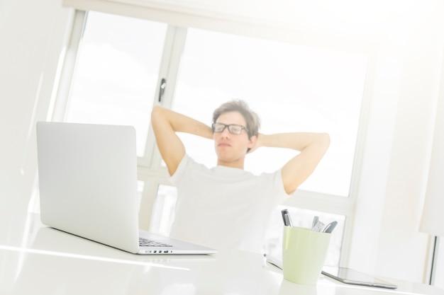 Mann, der vor laptop mit den händen hinter kopf sitzt