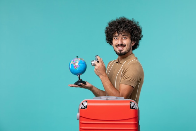 Mann der vorderansicht im urlaub, der kleine kugel und kamera auf blau hält