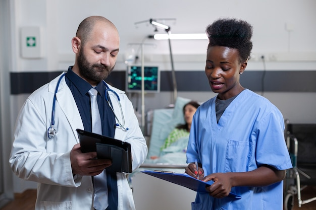 Mann, der während der ärztlichen konsultation mit einem schwarzen assistenten in der krankenstation diskutiert