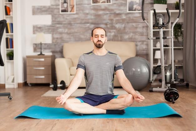 Mann, der während der globalen isolation achtsamkeit auf der yogamatte auf der matte praktiziert. schweizer ball im hintergrund.
