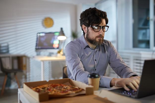 Mann, der während des mittagessens arbeitet