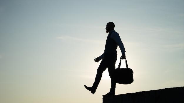 Mann, der während des sonnenuntergangs auf dem himmelshintergrund vom rand tritt. konzept des risikos und der wahl.