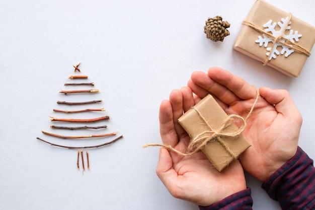 Mann, der weihnachtsgeschenk auf einem weißen hintergrund hält