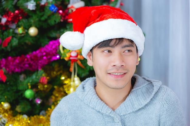 Mann, der weihnachtshut trägt, der mit freude lächelt
