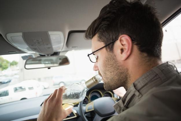 Mann, der wein beim fahren trinkt