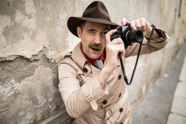 Mann, der weinlesekamera in einer stadtstraße verwendet