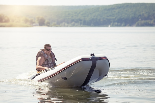 Mann, der weißes motorboot fährt
