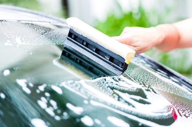 Mann, der windschutzscheibe während der autowäsche säubert