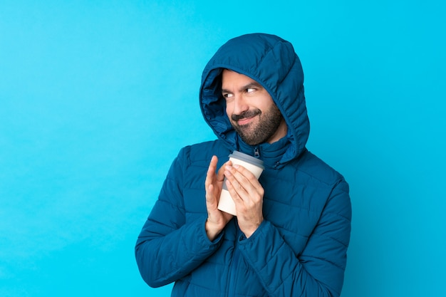 Mann, der winterjacke trägt und einen kaffee zum mitnehmen über isolierte blaue wand hält, die etwas entwirft