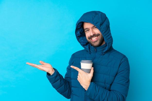 Mann, der winterjacke trägt und einen kaffee zum mitnehmen über isolierte blaue wand hält, die imaginären copyspace auf der handfläche hält, um eine anzeige einzufügen