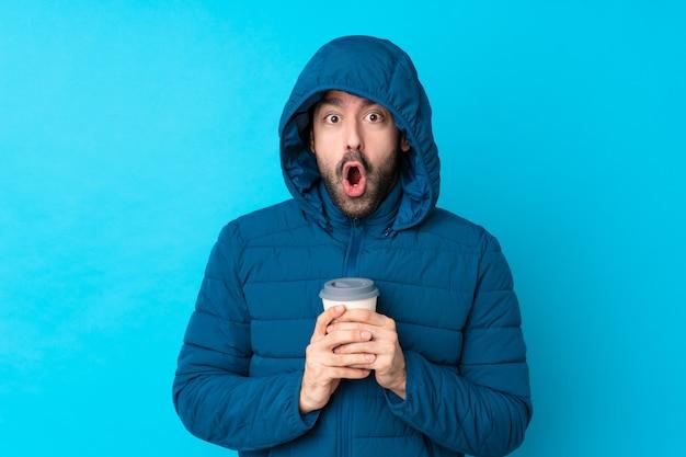 Mann, der winterjacke trägt und einen kaffee zum mitnehmen über isolierte blaue wand mit überraschendem gesichtsausdruck hält