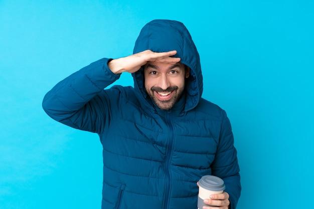 Mann, der winterjacke trägt und einen kaffee zum mitnehmen über isoliertem blau hält, das weit weg mit der hand schaut, um etwas zu schauen