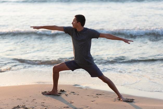 Mann, der yoga am strand tut