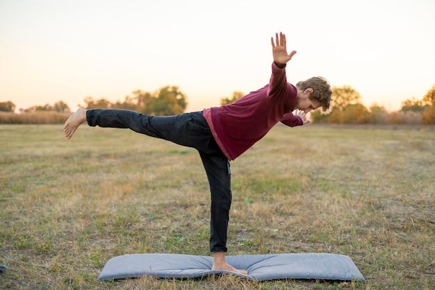 Mann, der yoga asana praxis auf dem gebiet tut