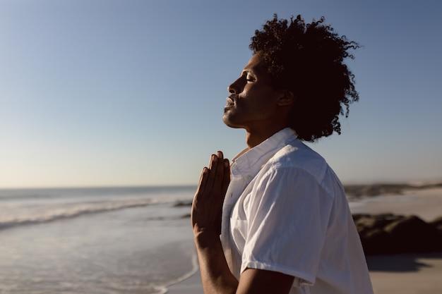 Mann, der yoga auf dem strand durchführt