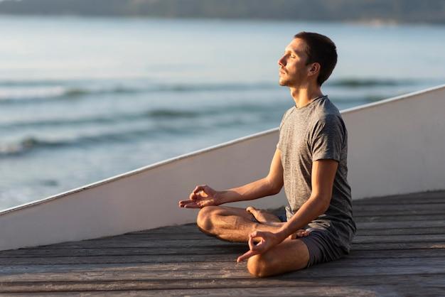 Mann, der yoga außerhalb nahe meer tut