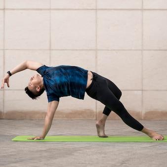 Mann, der yoga draußen auf matte mit kopienraum tut