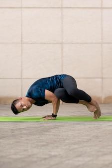 Mann, der yoga draußen auf matte tut