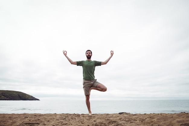 Mann, der yoga durchführt