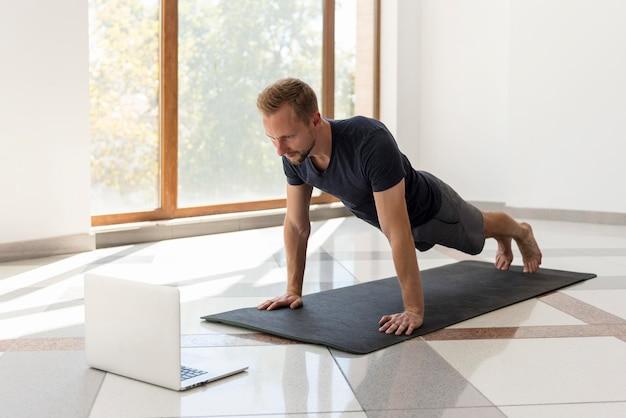 Mann, der yoga-haltung tut, die laptop betrachtet